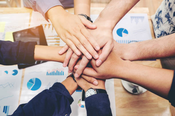 business teamwork joining hands team spirit collaboration concept - efficiency stock photos and pictures