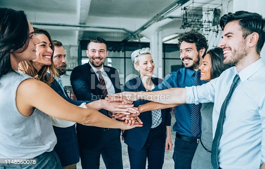 Group of business people with stacked hands showing unity and teamwork