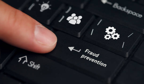 Business, technology, internet and networking concept. Young businessman working on his laptop in the office, select the icon Fraud prevention on the virtual display stock photo