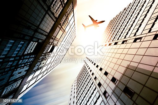 182061540 istock photo Business towers with a airplane silhouette 1074182736