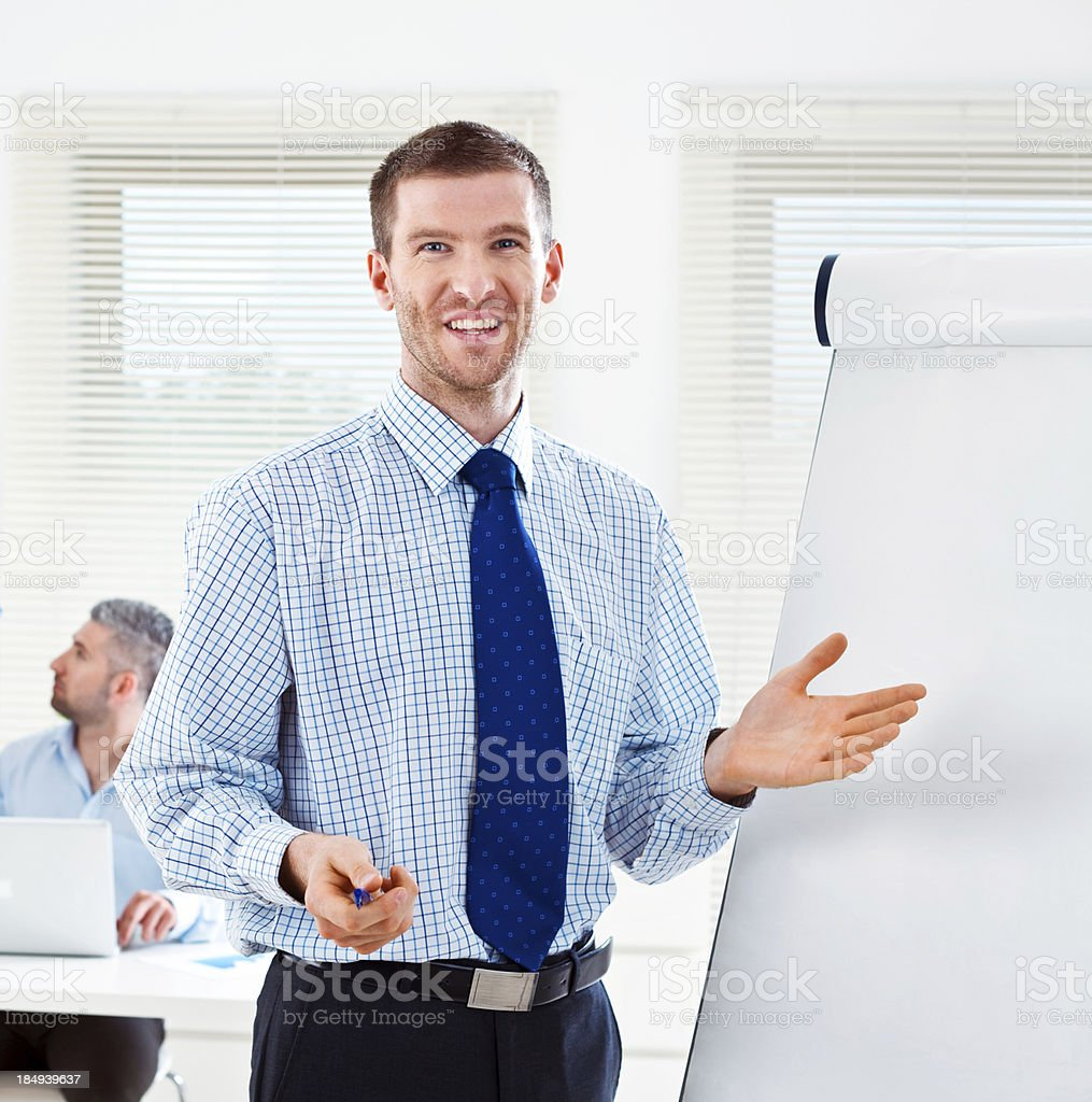 Business training Focus on happy businessman standing next to the flip chart and smiling at camera with his colleague working in the background. 30-34 Years Stock Photo