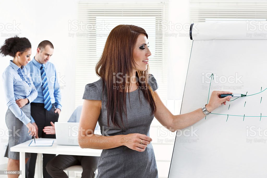 Business training Focus on the young businesswoman drawing graph on the flip chart with her colleagues working in the background. Adult Stock Photo