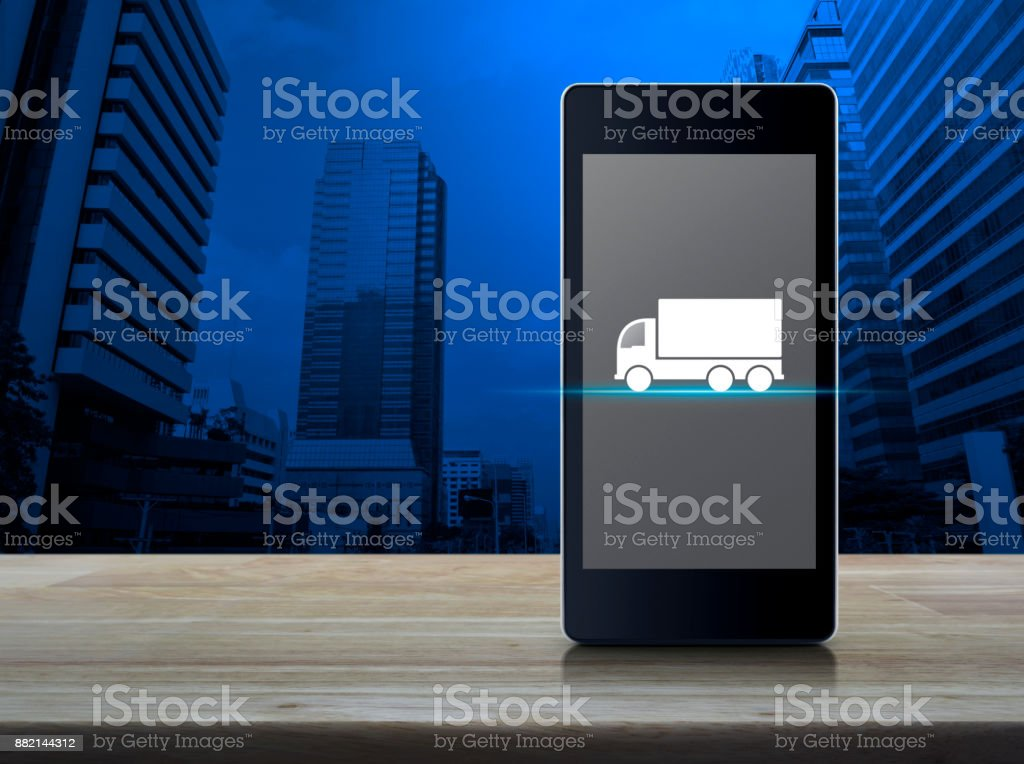 Business transportation service concept Truck flat icon on modern smart phone screen on wooden table over office city tower, Business transportation service concept Biological Cell Stock Photo