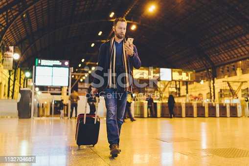 Businessman on business travel in Valencia using smartphone at the railroad station