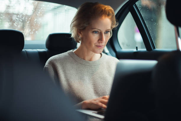 Business travel 40-year old business woman is traveling by car. She is sitting on the back seat and working on the laptop. georgijevic frankfurt stock pictures, royalty-free photos & images