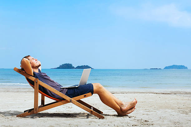 business travel smiling businessman with computer relaxing on the beach smooth stock pictures, royalty-free photos & images