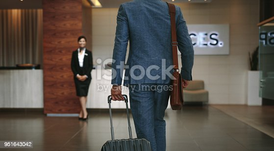 Businessman carrying suitcase while walking in hotel lobby. Business traveler arriving at hotel with female receptionist standing in background for welcoming.