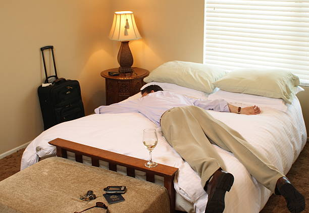 business traveler asleep on bed - man face down stock pictures, royalty-free photos & images
