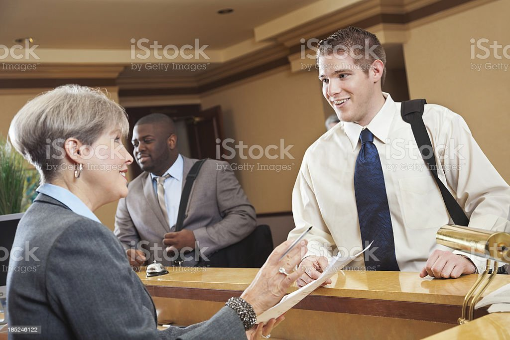 Business traveler checking hotel bill with the front desk associate royalty-free stock photo