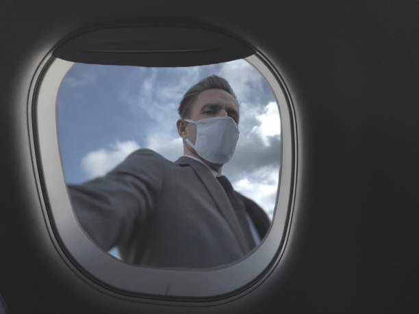 Business Traveler in Face Mask Taking Airplane Selfie stock photo