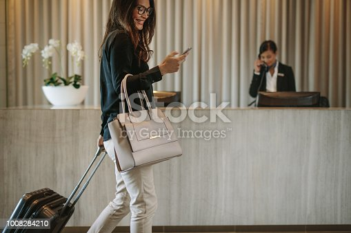 Woman using mobile phone and pulling her suitcase in a hotel lobby. Female business traveler walking in hotel hallway.