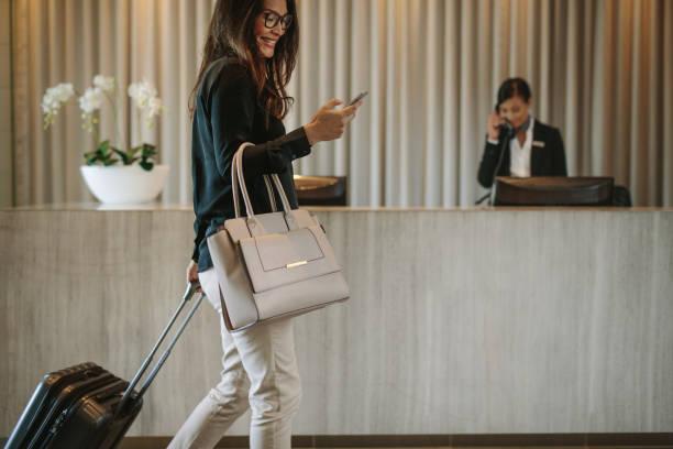 podróżny służbowy w korytarzu hotelowym z telefonem - hotel zdjęcia i obrazy z banku zdjęć