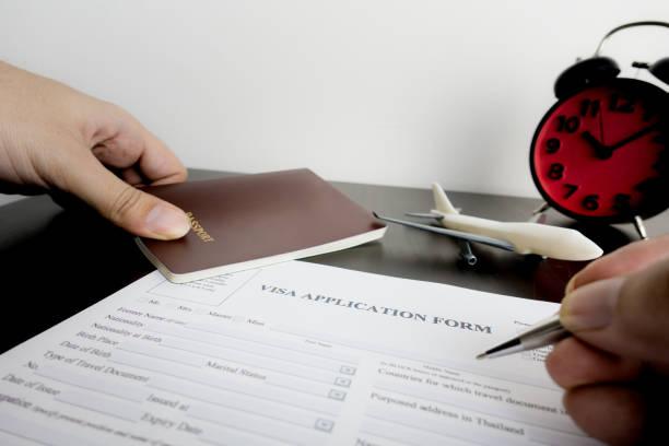 El viajero de negocios está llenando el formulario de Visa con el reloj de plazo - foto de stock