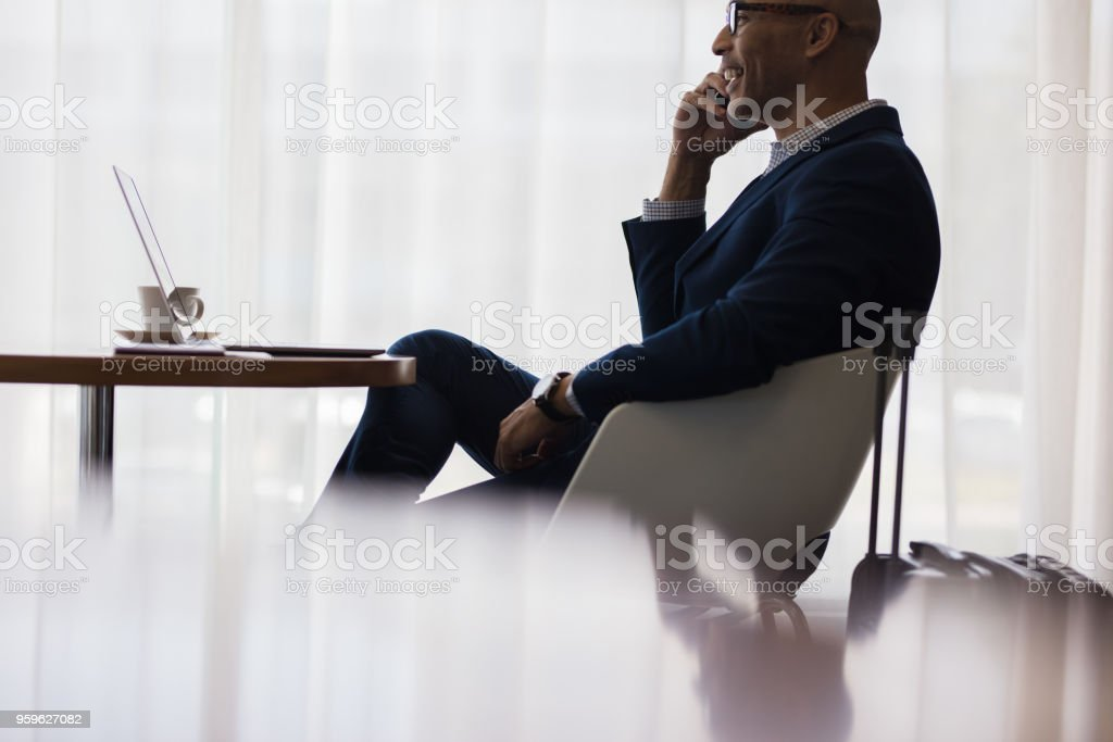 Business traveler making a phone call from airport lounge stock photo