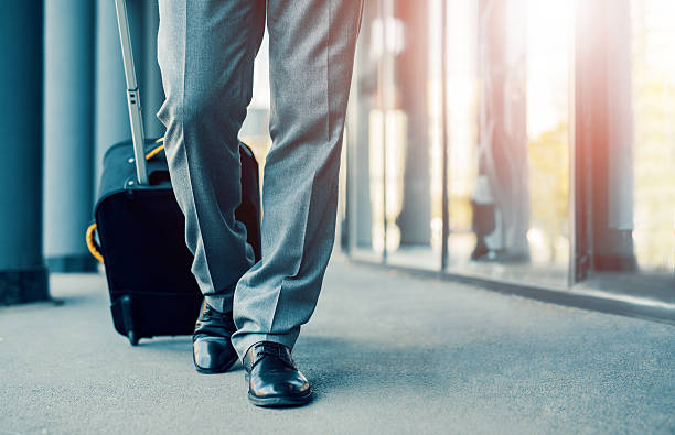 business traveler pulling suitcase - business travel stock photos and pictures