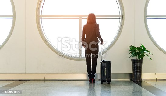 istock Business traveler stands at the airport in front of the windows waiting for her flight 1153679542