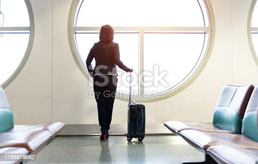 istock Business traveler stands at the airport in front of the windows waiting for her flight 1153679562