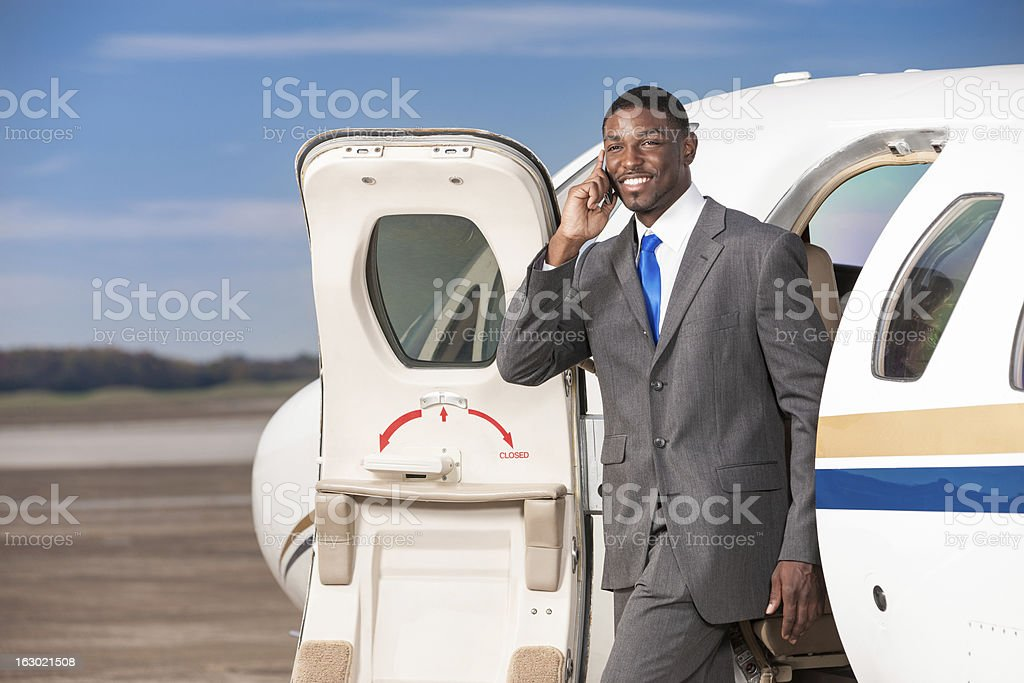 Business Traveler Talking on Phone in Doorway of Corporate Jet stock photo