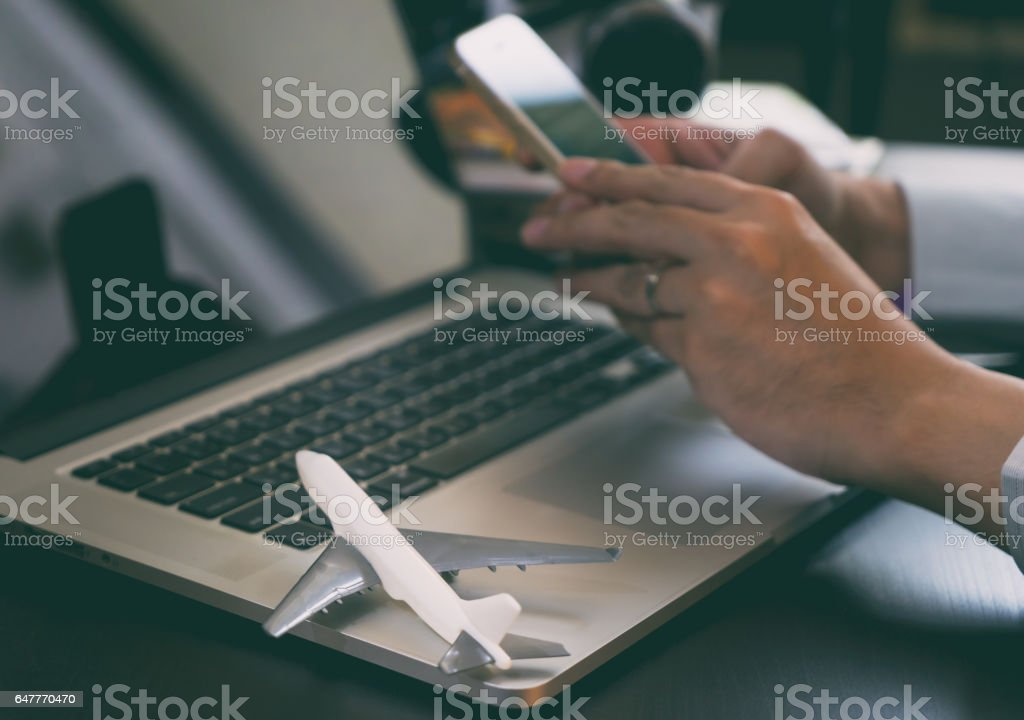 Business traveler using his phone to book his trip stock photo
