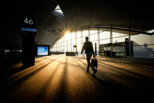 A business traveler walks towards departure gate in Hong Kong Airport stock photo