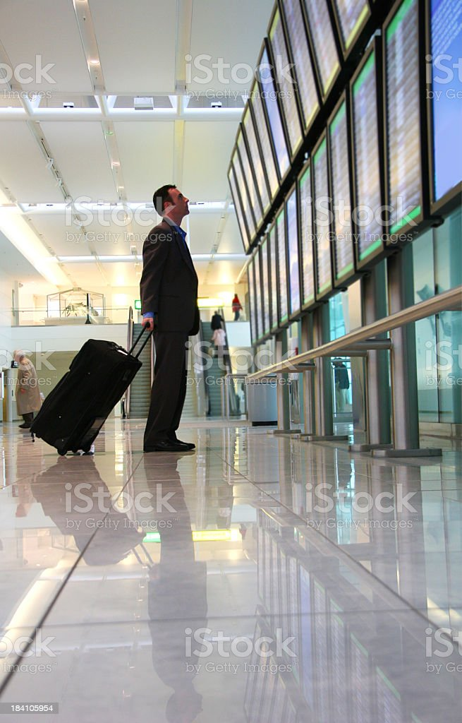 Business Traveler with luggage looks at departure schedule stock photo