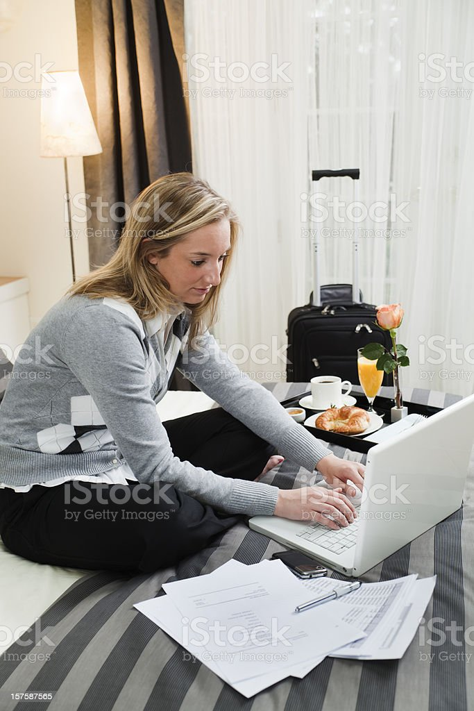 Business Traveler Working on Laptop with Hotel Room Service Breakfast royalty-free stock photo
