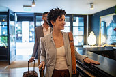 Business travelers arriving at hotel reception desk. Young businesswoman with male colleague walking in the hotel.