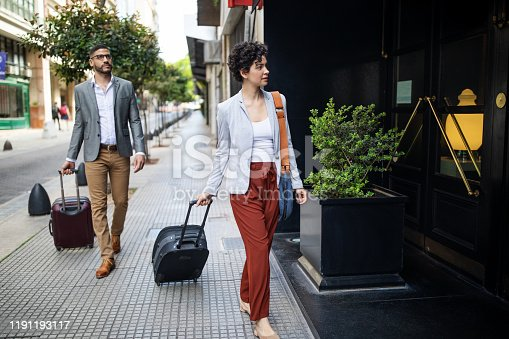 Business travelers arriving at their hotel. Young businesswoman with male colleague walking in to a hotel.