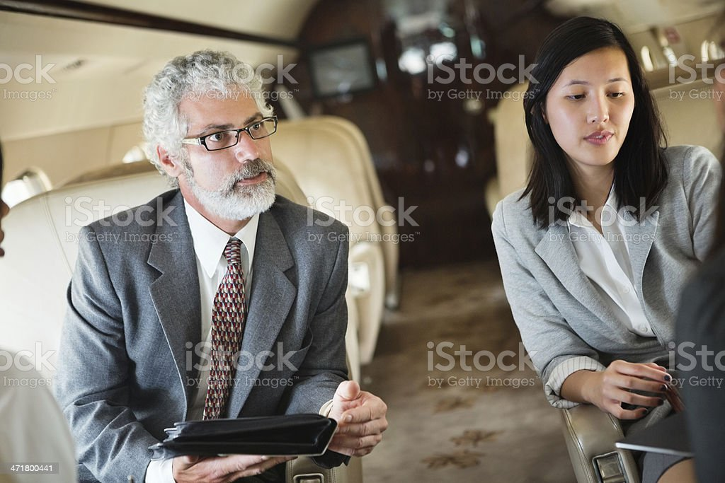 Business travellers working on board corporate private jet royalty-free stock photo
