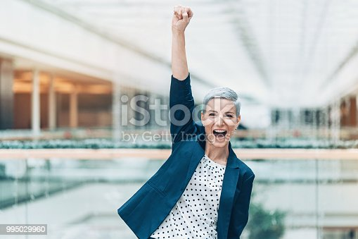 Excited businesswoman with arm raised in triumph