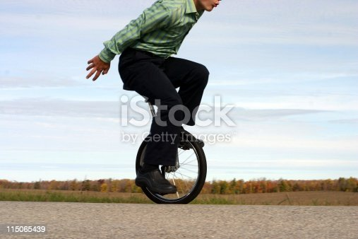 smartly dressed young man on unicycle
