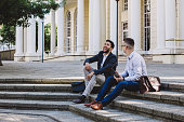 Shot of two young businessmen sitting on steps and using a digital tablet in the city