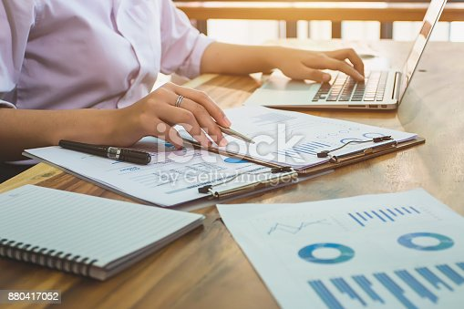 istock business woman accountant working with financial reports and laptop computer 880417052