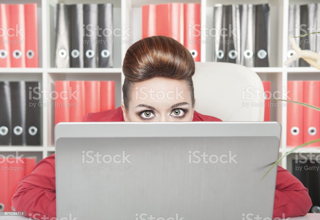 Business woman afraid and hiding behind the computer royalty-free stock photo