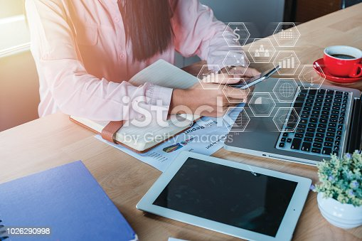 Business woman analyzing financial data on smartphone and laptop computer. Business analysis and strategy concept with virtual graphic icon diagram.