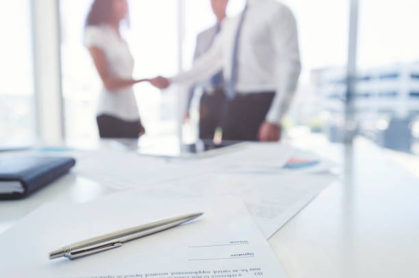 Business woman and business man shaking hands with a contract. Business woman and business man shaking hands with a contract. There is a pen on the contract document. Focus is on the foreground with the three people in the office out of focus in the background. They are wearing formal corporate business clothes. dealing cards stock pictures, royalty-free photos & images