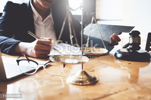 istock Business woman and lawyers discussing contract papers with brass scale on wooden desk in office. Law, legal services, advice, Justice and real estate concept. 1145545389