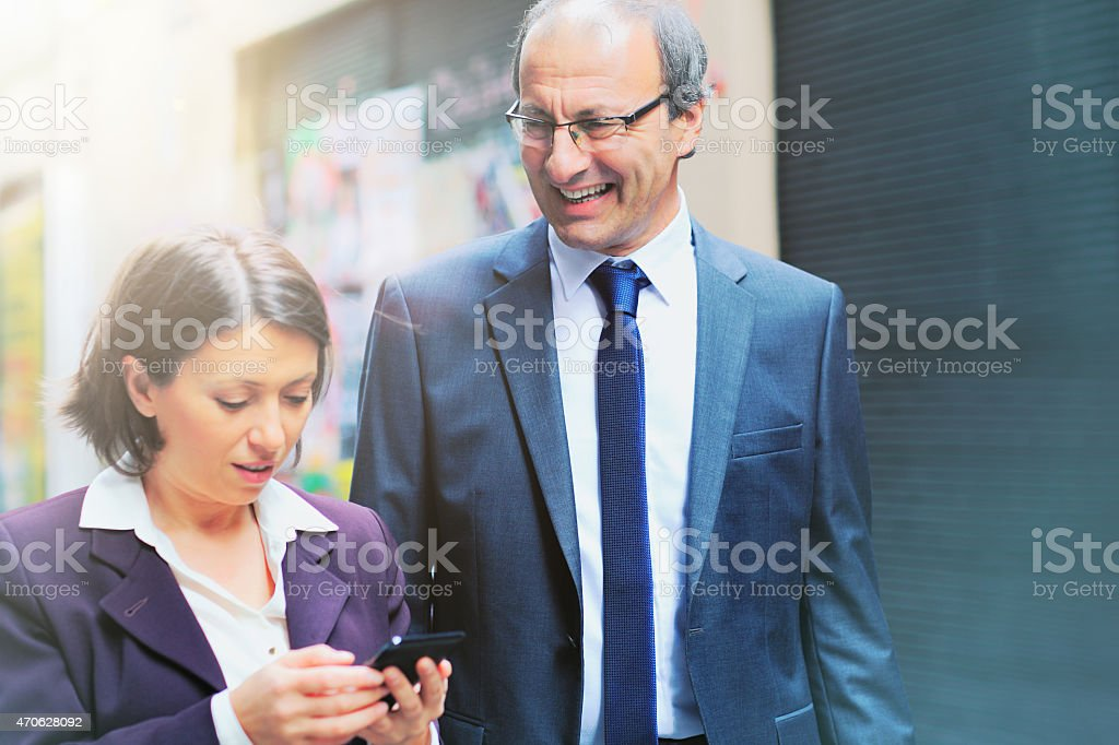 Business woman and man looking at mobile phone.on the streets of...