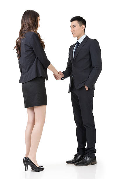 Business woman and man shake hands stock photo