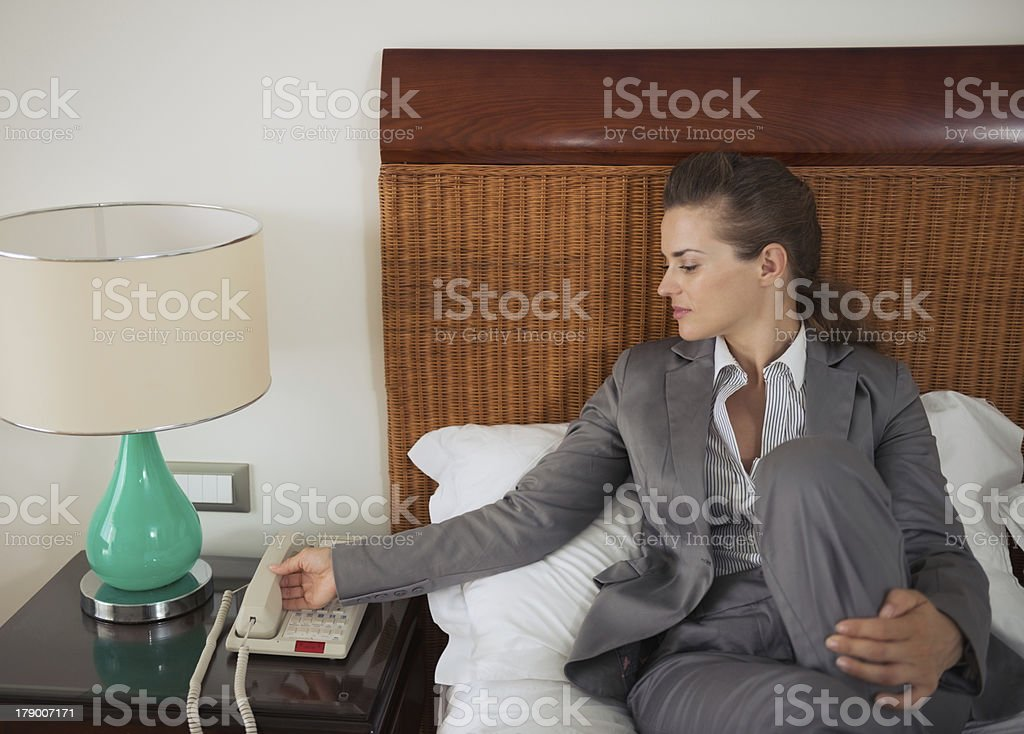 Business woman answering phone call on bed in hotel room royalty-free stock photo