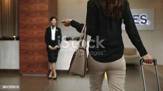Rear view of business woman arriving at hotel with luggage. Female concierge standing in background for welcoming the guest.