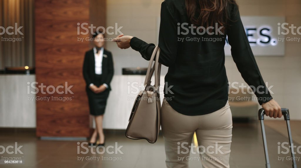 Business woman arriving at hotel with luggage stock photo