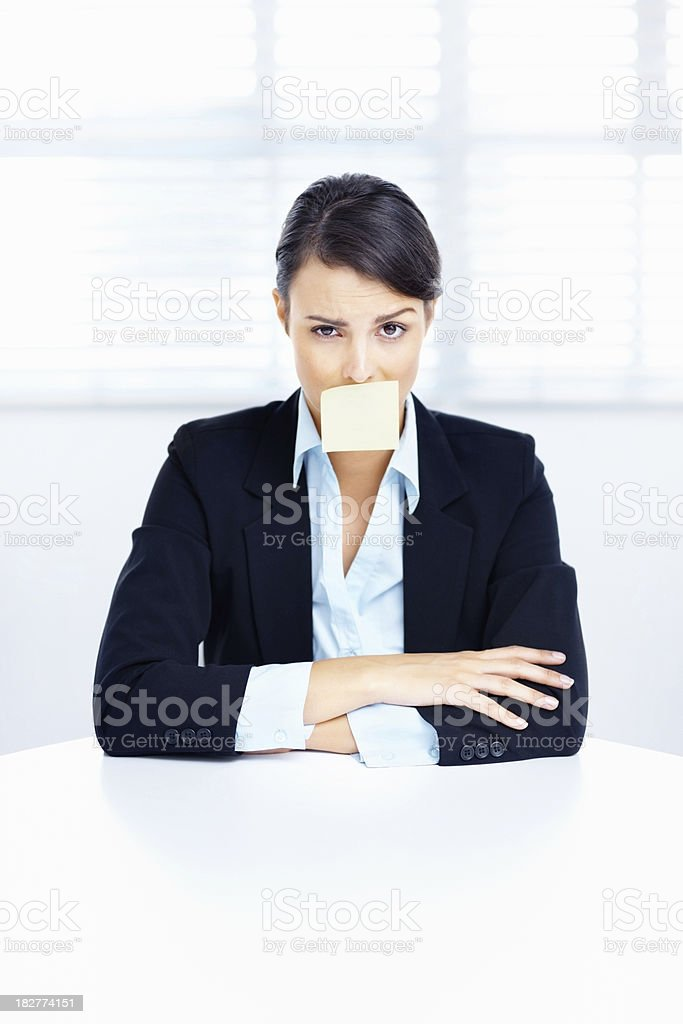Business woman at a table with adhesive note on mouth royalty-free stock photo