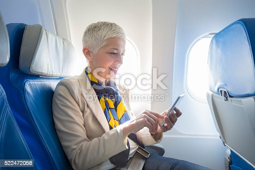 istock business woman at airplane 522472058