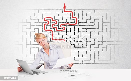 846409842 istock photo Business woman at desk with labyrinth and arrow 1158572621