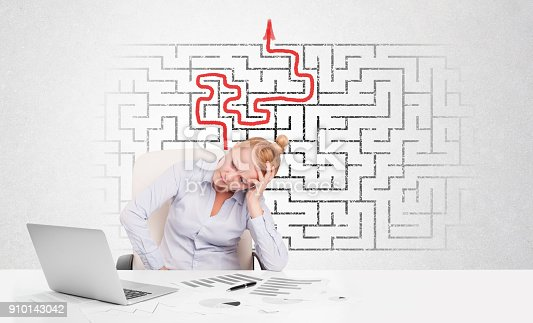 istock Business woman at desk with labyrinth and arrow 910143042