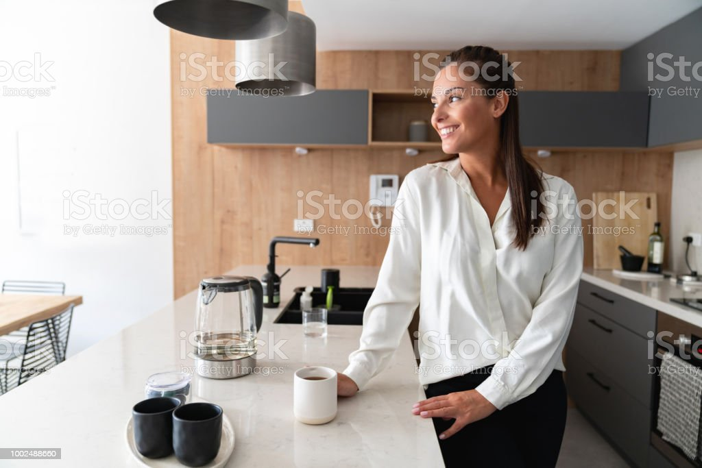 Business woman at home making a cup of coffee stock photo