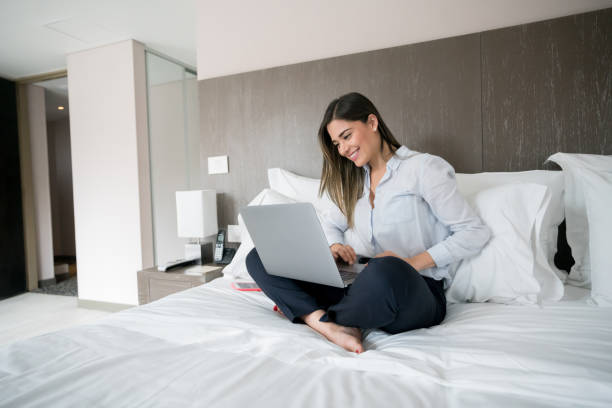 business woman at home working on a laptop on the bed - guest stock pictures, royalty-free photos & images