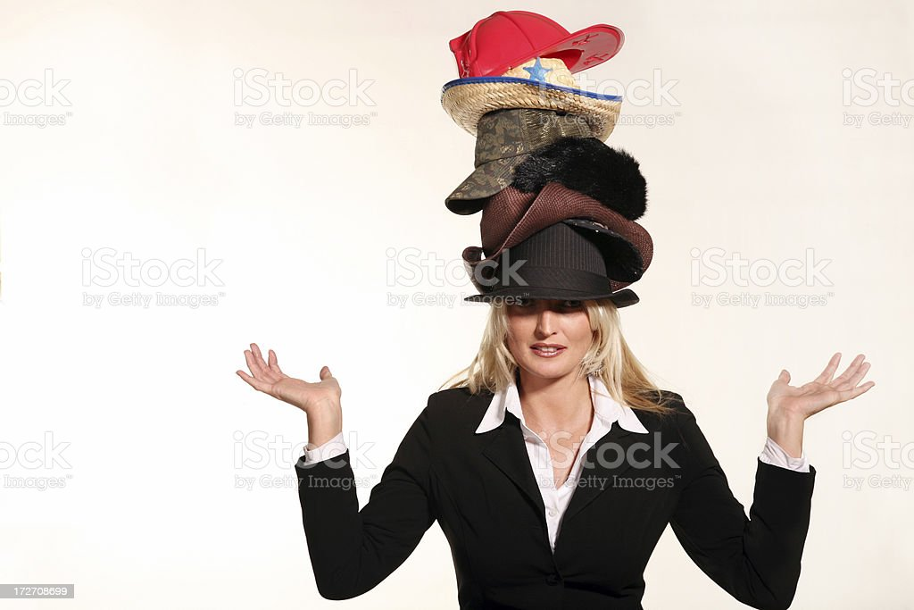 Business woman balancing life having to wear too many hats stock photo