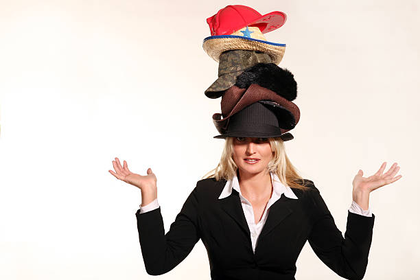 Business woman balancing life having to wear too many hats In todays busy world, many of us have to wear many hats.  Having to be a business woman,put out fires,hunt for  leads,play like a kid, and many of things. medium group of objects stock pictures, royalty-free photos & images